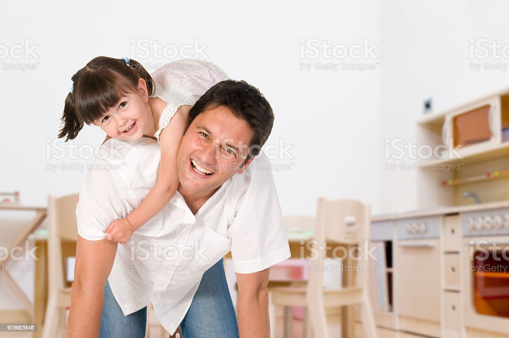 Little girl on her father's back playing as they both laugh royalty-free stock photo