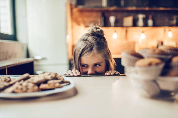 kleines mädchen in der küche. - kekskuchen stock-fotos und bilder