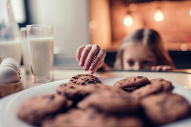 kleines mädchen mit küche - schokoladenplätzchen stock-fotos und bilder