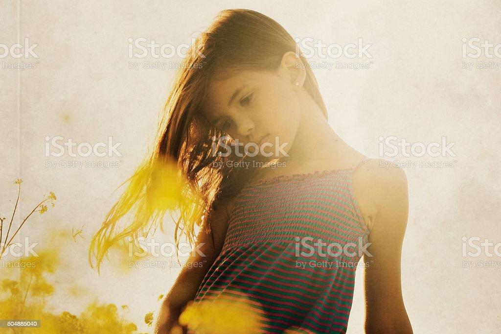 Little girl on meadow of flowers stock photo
