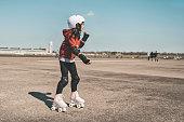 Side view on little girl on roller skates on Tempelhofer Feld in Berlin