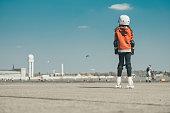 Rear view on little girl on roller skates on Tempelhofer Feld in Berlin