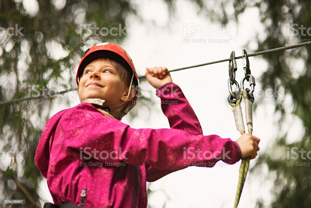 Little girl on ropes course in adventure park stock photo
