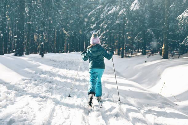 kleines Mädchen auf Ski in sonnigen verschneiten Winterwald – Foto