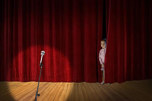 little girl on stage - mädchen vorhänge stock-fotos und bilder