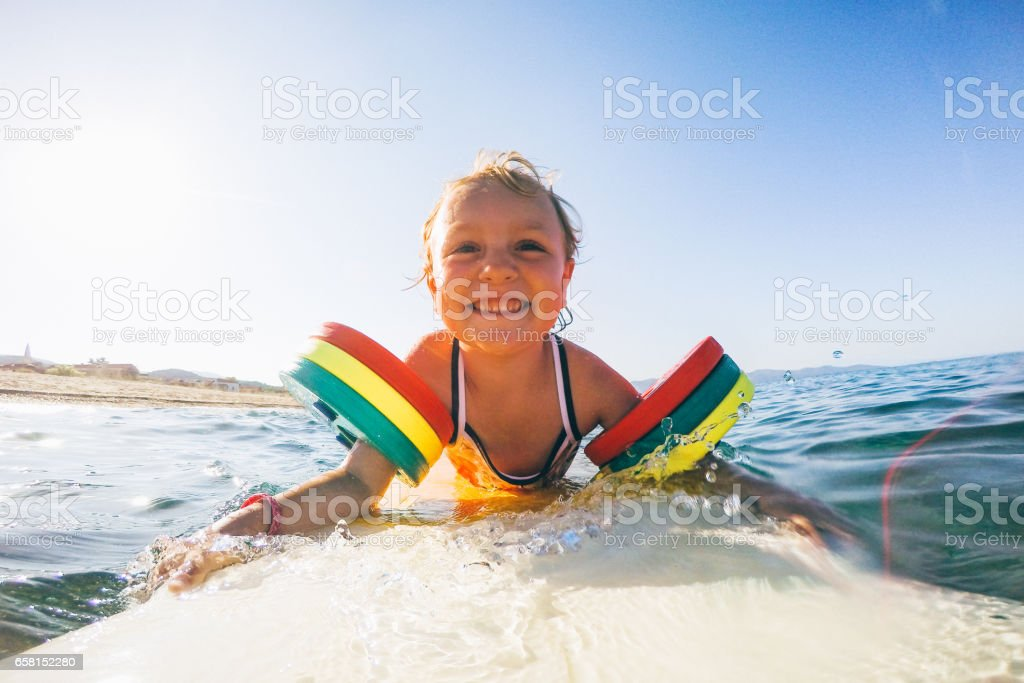 Little girl on surfboard stock photo