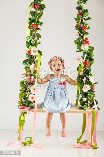 Little girl on flower decorated swing