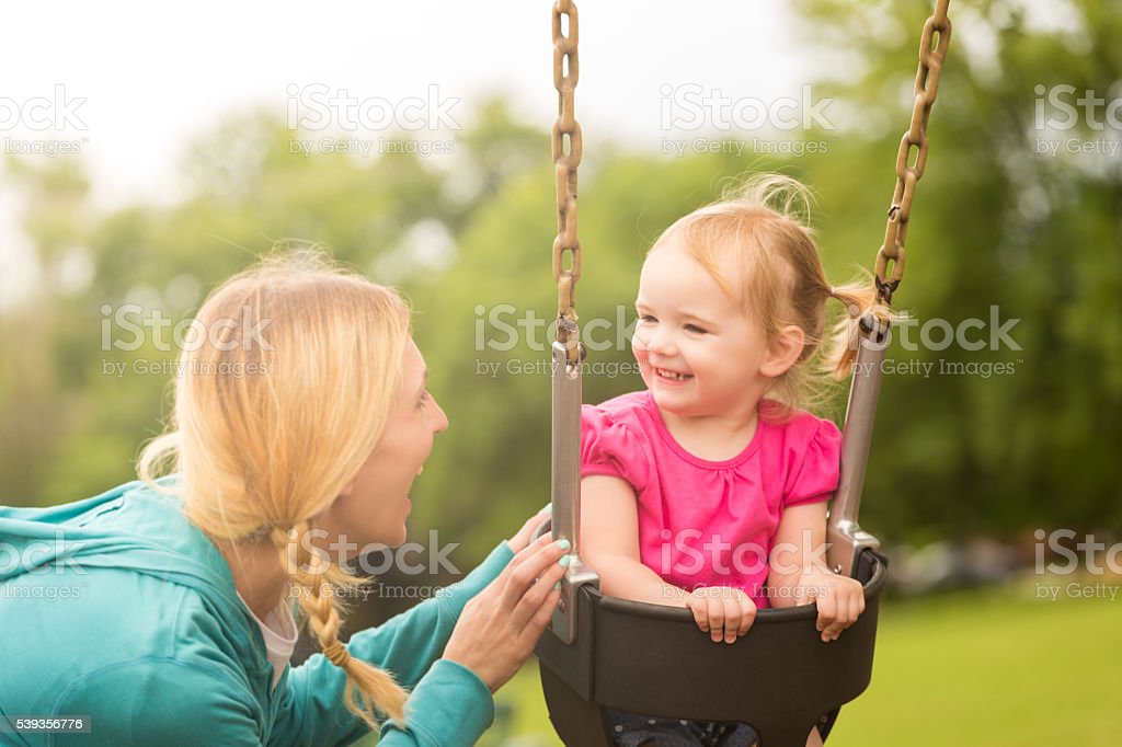 Little girl on swing smiling at her mom stock photo