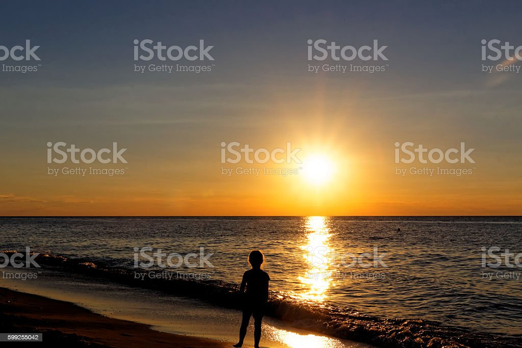 Little girl on the beach during sunset over the sea. – zdjęcie