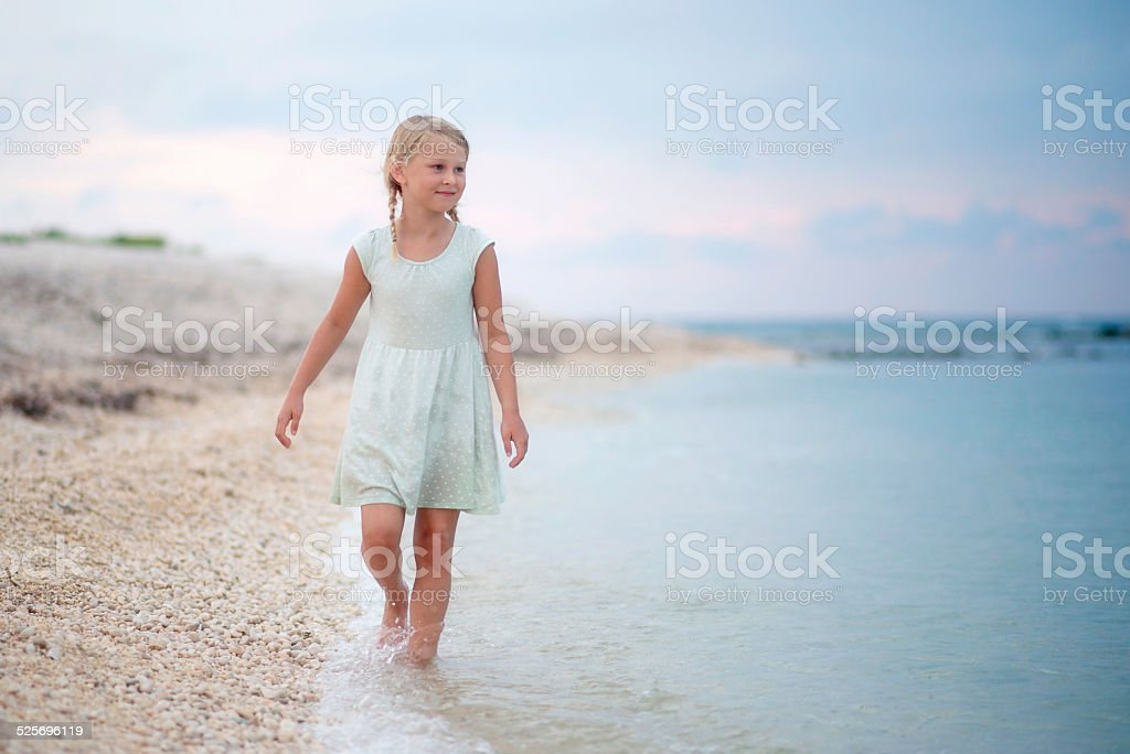Little Girl on the Beach on Cloudy Day stock photo