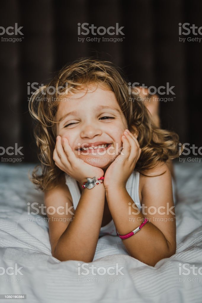 Little girl on the bed stock photo