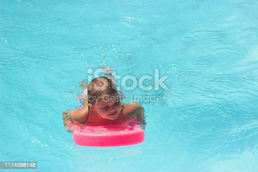 1159904048istockphoto Little girl on the floating board, learns to swim in the pool 1174098148