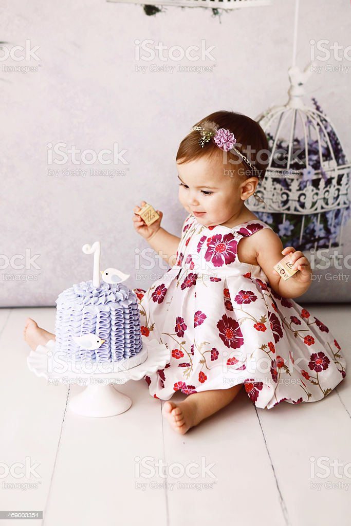Little girl on the floor looking at her first birthday cake stock photo
