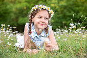 a little sweet girl lying on the grass. little girl and daisies. wild flowers