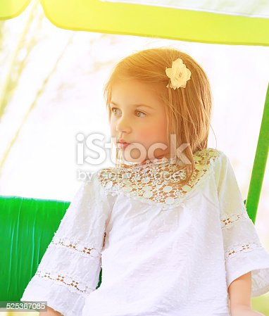 Portrait of adorable little girl riding on a swing outdoors in sunny day, summertime activities, having fun at daycare, happy childhood concept