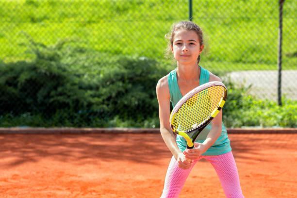 Little girl on the tennis court stock photo