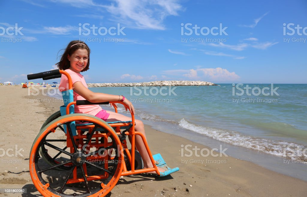 little girl on the wheelchair with metal wheels on the beach stock photo