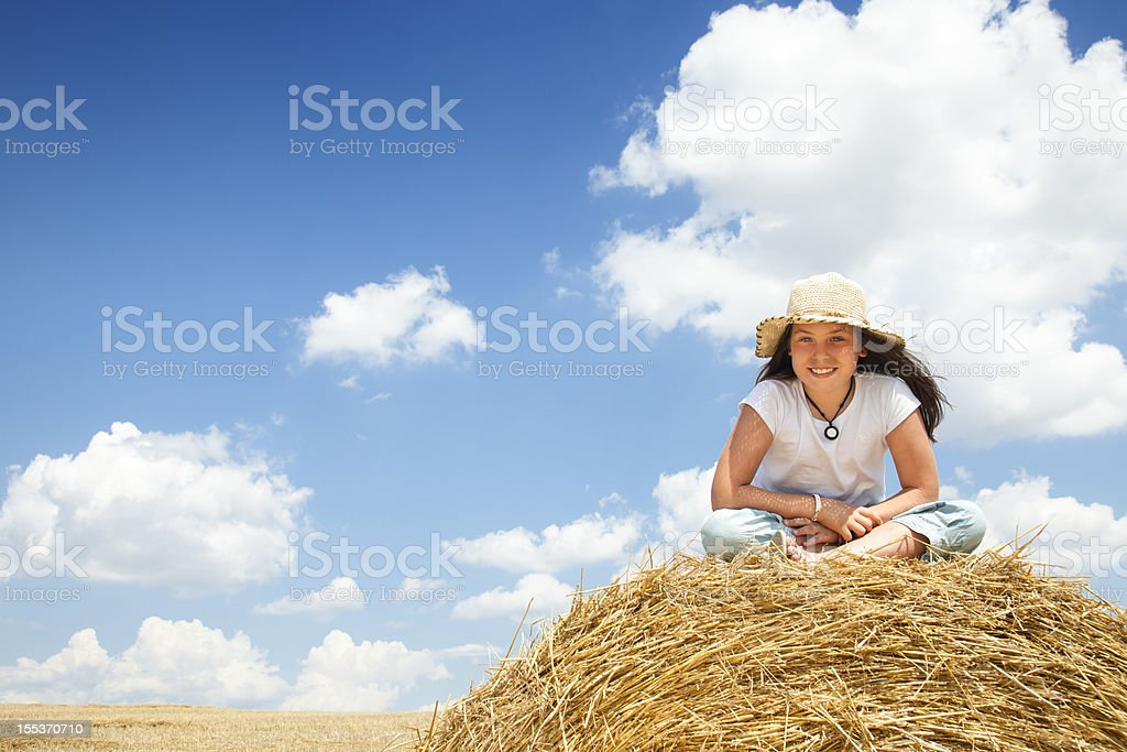 Little girl on top of hay bale royalty-free stock photo