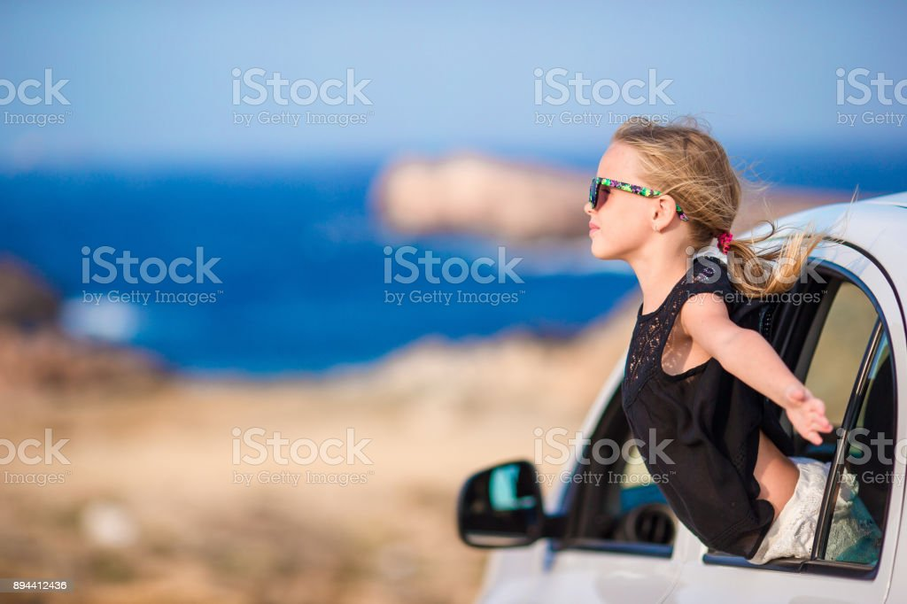 Little girl on vacation travel by car background beautiful landscape stock photo