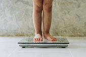 istock little girl on weight scale on floor background, Diet concept. 1203585953