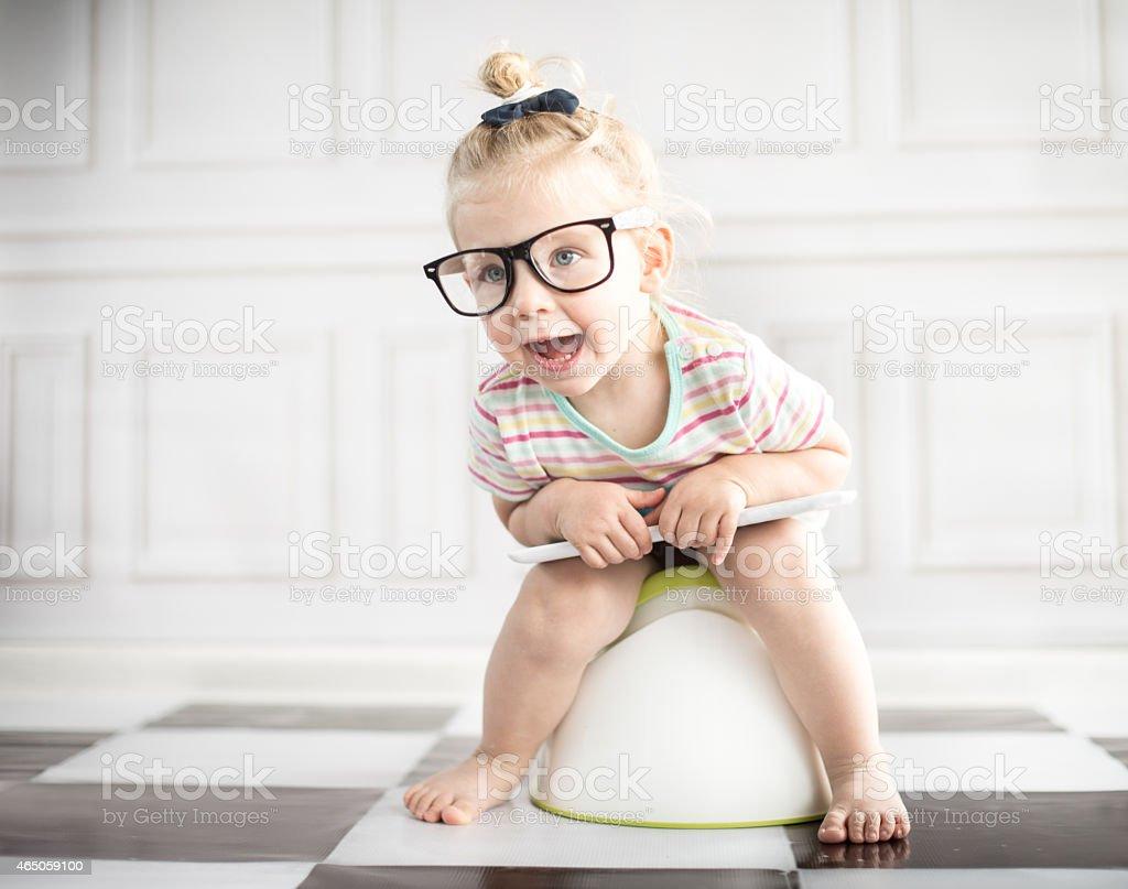 Kleines Mädchen auf weißer Töpfchen mit digitalen tablet – Foto