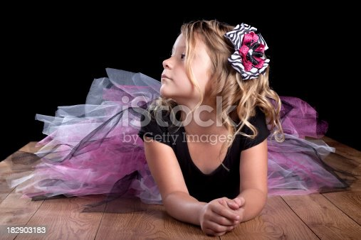Cute little girl looking at camera with serious expression. Wearing pink and purple tutu.