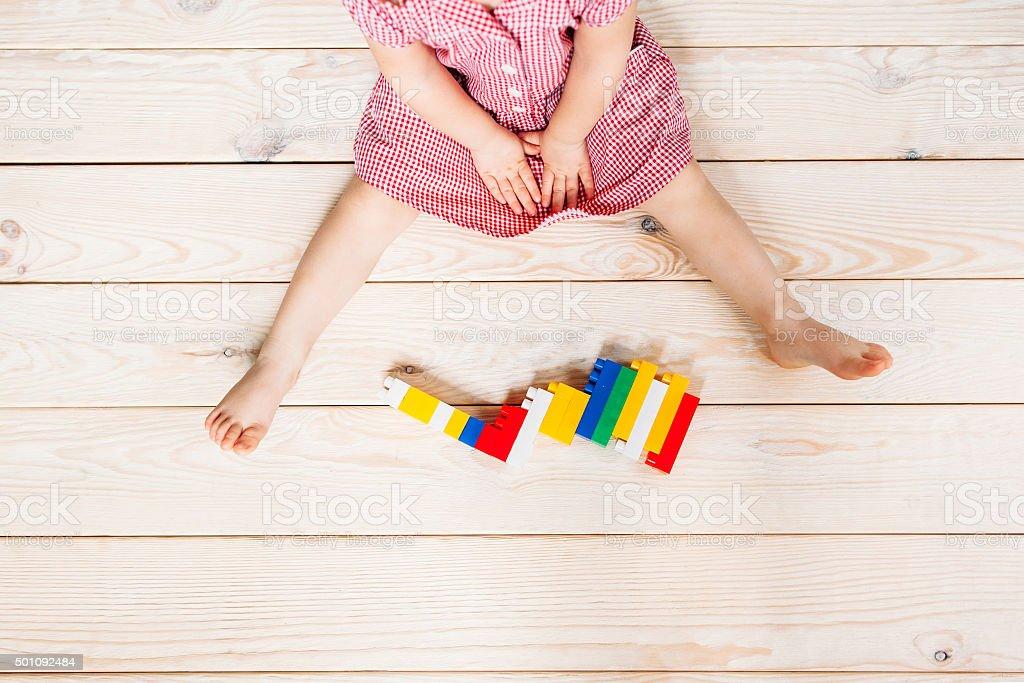 little girl on wooden floor playing blocks stock photo