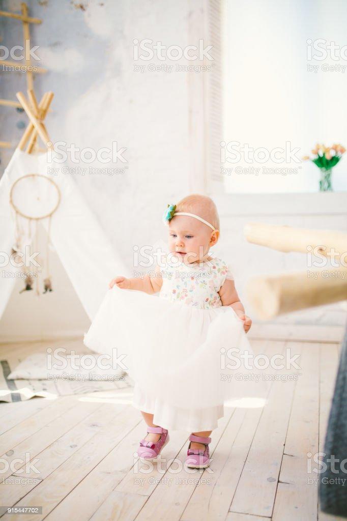 24871cee5f5f1d meisje eenjarig met blauwe ogen Blond in een weelderige witte jurk is blij  en speelt in