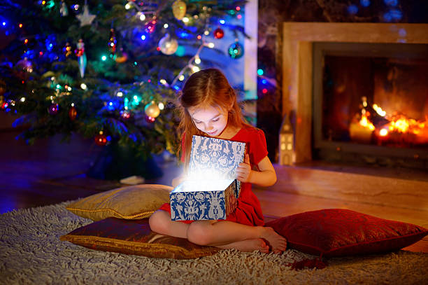 little girl opening a magical christmas gift - little girls giving head stock photos and pictures