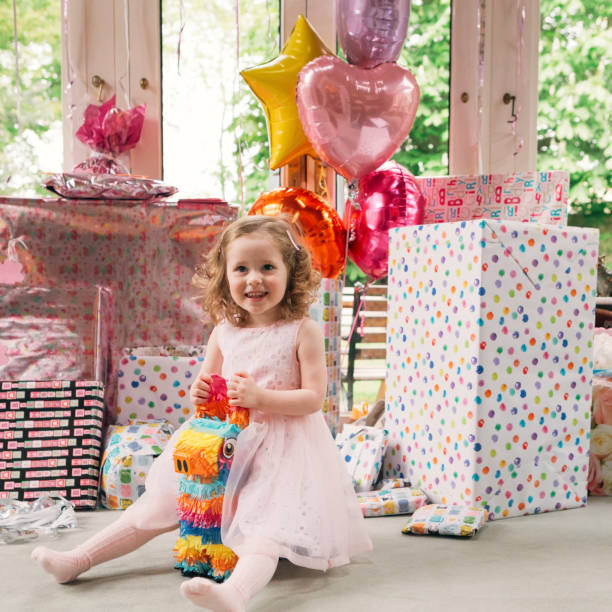 Little Girl Opening Birthday Presents A little girl is enjoying her birthday party at home with family birthday wishes for daughter stock pictures, royalty-free photos & images