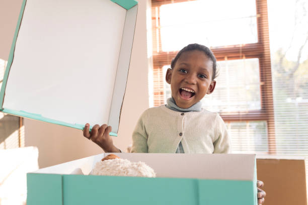 Little girl opens moving box of toys smiling at camera stock photo