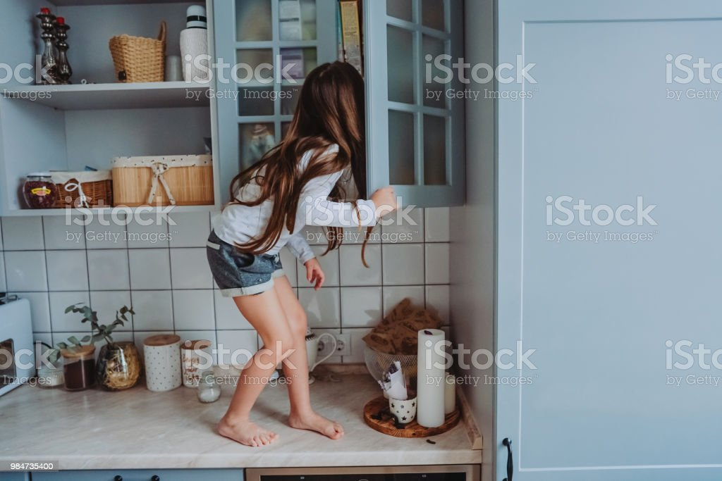 little girl opens the closet stock photo