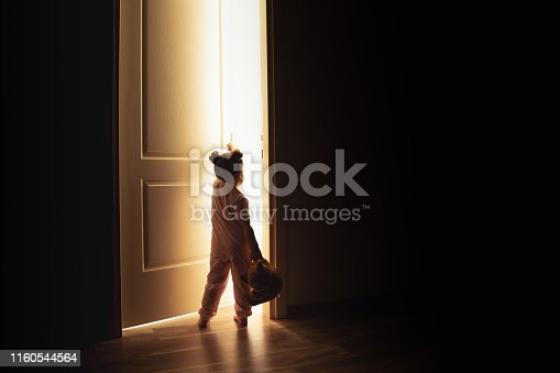 Little girl opens the door to the light in darkness.