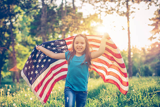 Little girl outdoors in a meadow on july 4th stock photo