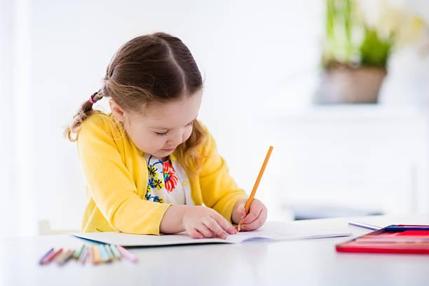 kleines mädchen malerei und literatur - zeichnen lernen mit bleistift stock-fotos und bilder