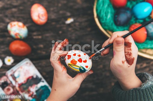 Overhead view on Childs hand painting easter eggs on old wooden table