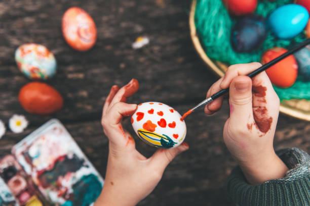 오래 된 나무 테이블에 부활절 달걀을 그리는 어린 소녀 - 부활절 달걀 뉴스 사진 이미지