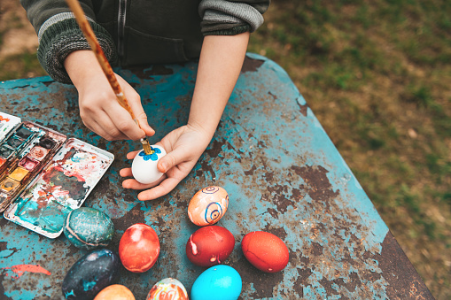 Overhead view on girl painting easter eggs on old blue table in the garden