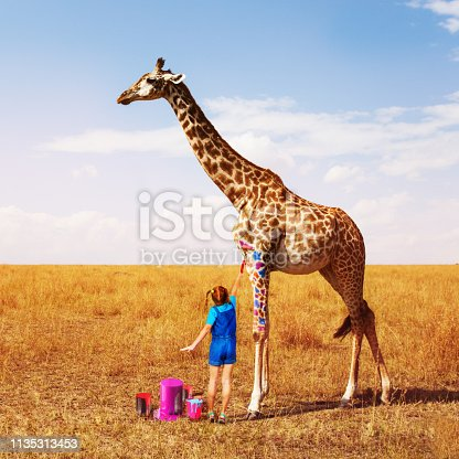 Little girl painting African giraffe into different colors dreaming concept
