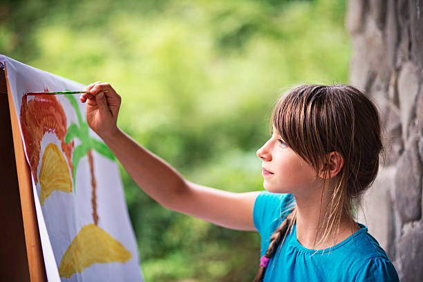 little girl painting on easel in the garden - mädchen malen stock-fotos und bilder