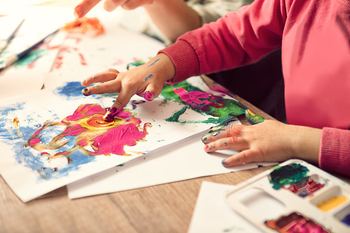 istock Little girl painting with finger 1133604445