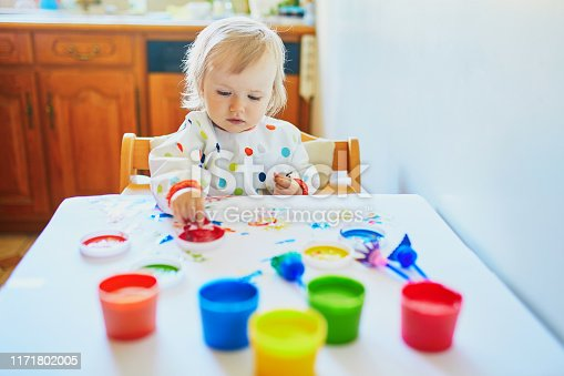 istock little girl painting with fingers at home 1171802005