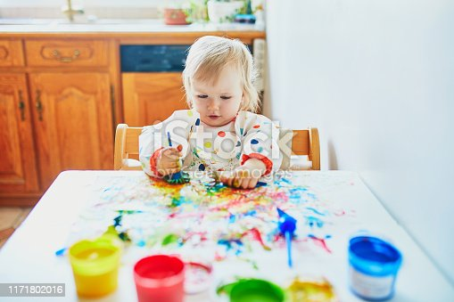 istock little girl painting with fingers at home 1171802016