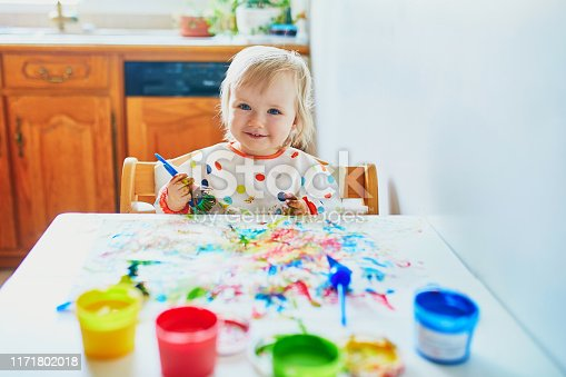 istock little girl painting with fingers at home 1171802018