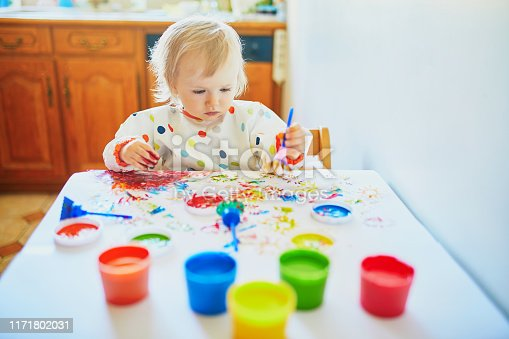 istock little girl painting with fingers at home 1171802031