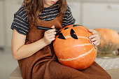 istock little girl paints a pumpkin for Halloween. preparation for halloween. Halloween holiday and family lifestyle background. selective focus 1282737671