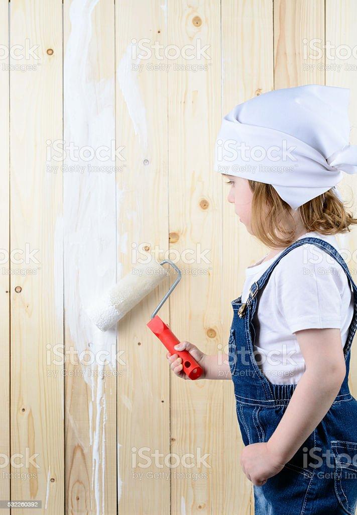 Niña pequeña pintura de una pared de madera - foto de stock
