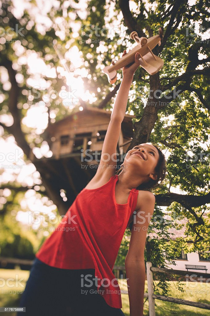 Little girl palying under a tree with toy wooden plane stock photo