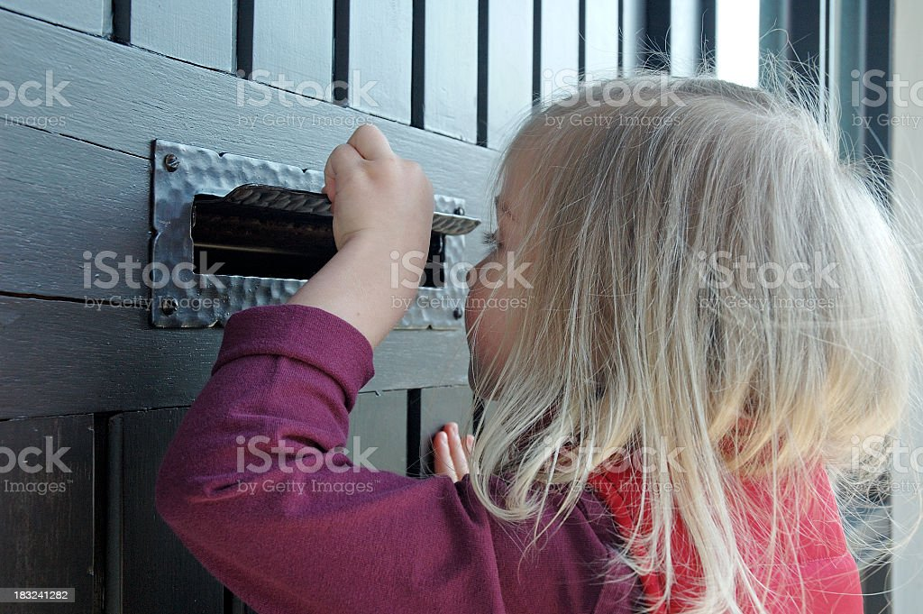 A little girl peeking through a mail slot on a house  royalty-free stock photo