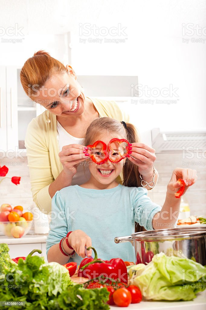 little girl peeking through a red pepper for healthy eating. royalty-free stock photo